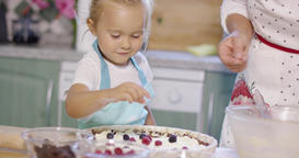 Smiling little girl adding berries to a pie Footage