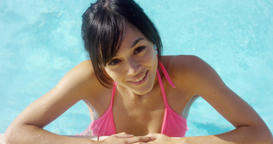 Smiling brunette in pink bikini stands in pool 영상물