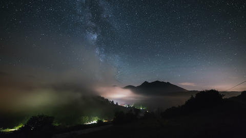 Stars with milky way galaxy moving over mountains above foggy valley in starry Footage