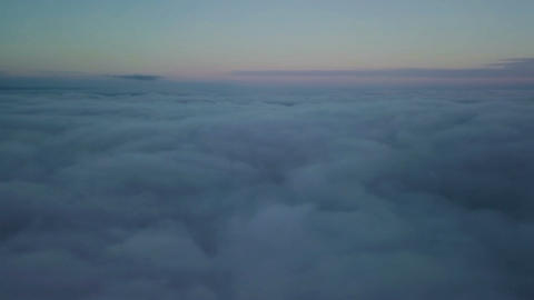 Epic flight down into the clouds at morning sunrise. Aerial slow motion drone Footage