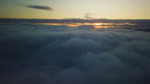 Epic flying above clouds at sunrise. Aerial slow motion with golden morning Footage