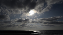 Sun and clouds with human figures on beach Footage