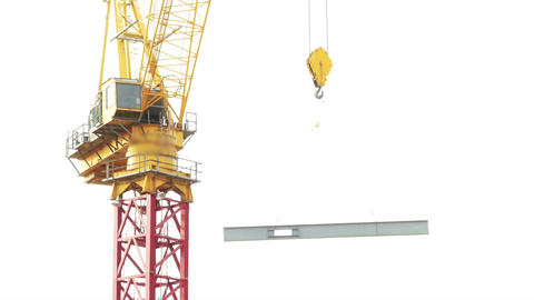 Tower crane lifting and moving I beam across frame with faces and logos blurred  Footage