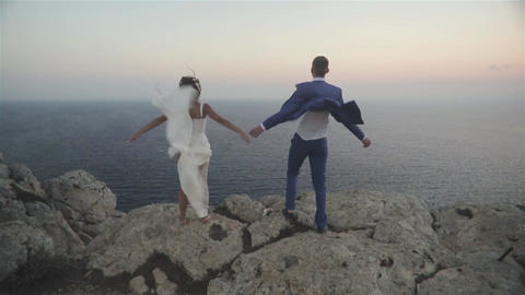 Wedding Couple Stands On A Cliff Above A Sea stock footage