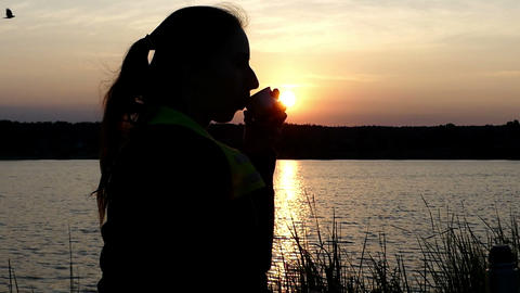 Nice woman sits on a lake bank drinking tea from a thermos 영상물