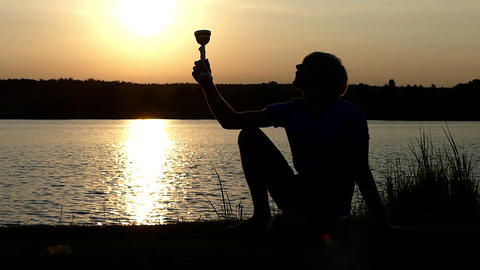 Sportsman takes a winner bowl from a lake bank and raises it in slo-mo Footage