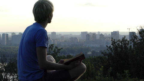 Creative man reads a book on the observation deck in Kyiv in slo-mo Footage