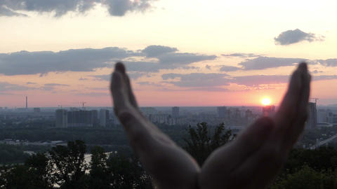 Creative man keeps the sun in his hands at sunset in Kyiv in slo-mo Footage