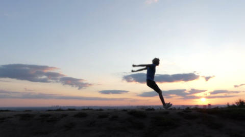 Blond man runs and jumps on a lawn at sunset in slo-mo 画像