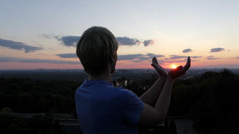 Young man keeps sun in his hands at sunset in Kyiv in slo-mo Footage