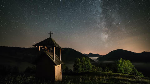 Stars with milky way galaxy moving over wooden belfry in mountains and foggy Footage