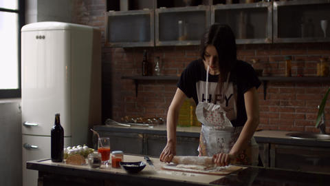Woman rolling out dough with rolling pin at home Footage