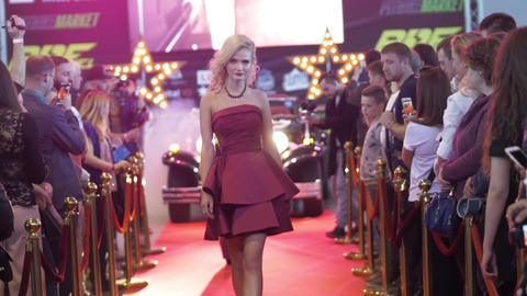 Attractive blonde model in red dress walking from retro car on red carpet Live Action