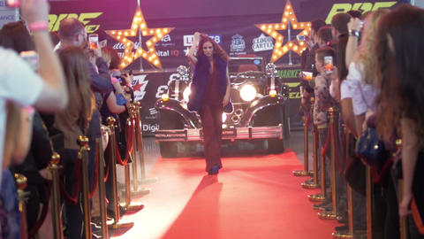Attractive female model in red dress walking from retro car on red carpet Live Action