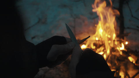 Male hands sharpens pencil over campfire with switchblade knife Footage