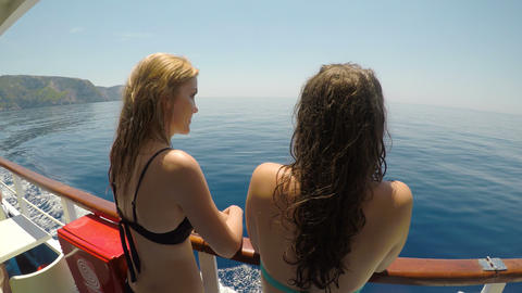 Relaxed young female tourists friends traveling on a sailboat looking the sea Footage