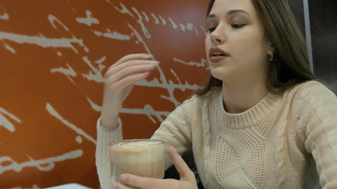 A sad girl is sitting in a cafe. She is sadly waiting for her boyfriend Footage