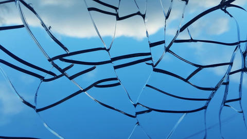 broken window with mesh cracks overlooking the sky and clouds GIF