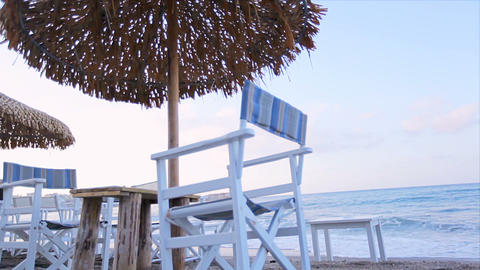 Relax on the beach in a deckchair under an umbrella Footage
