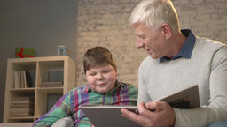 Elderly man teaches a young fat guy how to read. Grandfather and grandson, happy Footage