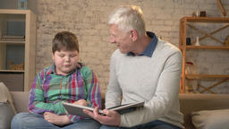 Elderly man is teaching a young fat guy. Grandfather and grandson, happy family Footage