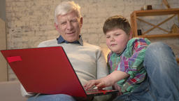Young fat boy teaches grandpa how to use a laptop. Difference of generations Footage