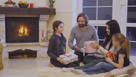 Family exchanges christmas gifts in the christmas evening near fireplace Footage