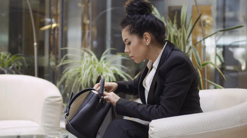 Businesswoman searches something in her bag Footage