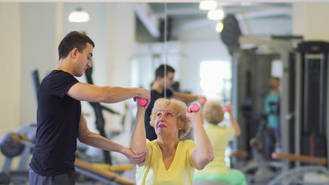 Elderly woman makes exercise with dumbbells in the gym with trainer Footage