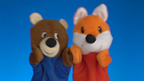 Funny glove puppets over blue background Footage
