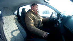Man gets into the car and starts driving on a winter road Footage