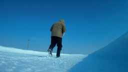 Man is walking along a winter road near the camera and going further Footage