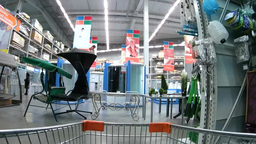 Shopping cart moving through supermarket aisles among household goods Footage