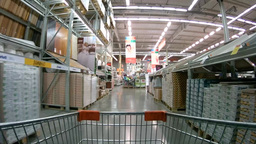 Shopping cart moving in supermarket between shelves with construction materials Footage