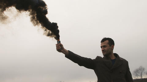 Serious man holding smoke bomb with black fume Footage