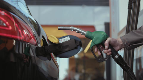 Multiple shots of a gas pump inserted in car tank Footage