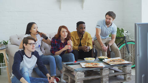 Group of young friends watching sports match on TV together eating snacks and Footage