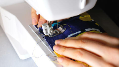 Woman sews on the sewing machine completes sewing close-up, 4k Footage