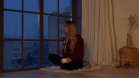Dreamy woman with coffee looking through window Live Action