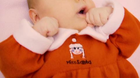 Cute little baby wearing red dress lies on bed Footage