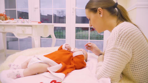 Young mother nurses a two-month girl in red santa's dress 영상물
