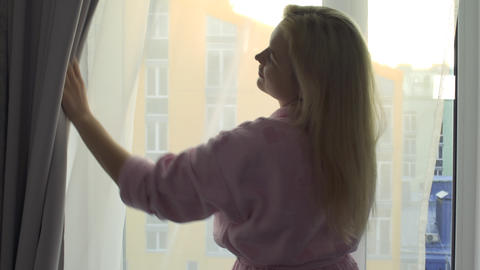 Young woman in domestic bathrobe just woke up open curtains in the morning Footage