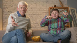 Grandfather and grandson are sitting on the couch and watching TV, eating chips Footage