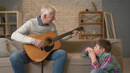 Grandpa plays for his grandson on guitar, music. A young fat guy is sitting on Footage