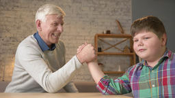 Grandfather and grandson arm wrestle in a cozy room at... Stock Video Footage