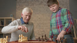 Grandfather and grandson are preparing to play chess. An elderly man teaches a Footage