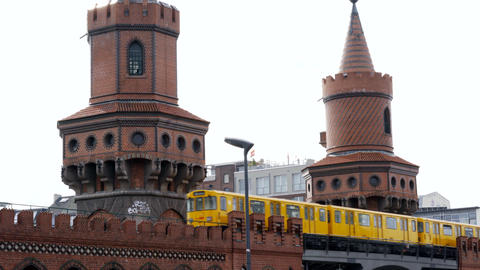 Yellow typical Berliner Tram Train Subway passing by Oberbaum Bridge in Berlin ビデオ