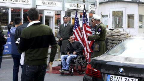 Man on a wheelchair taking photos and having fun with soldiers in uniform at Footage