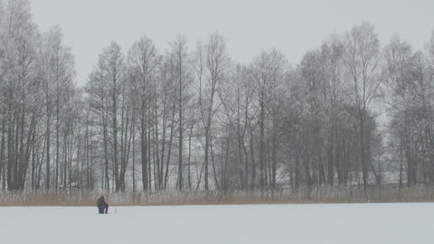 Winter fishing. Lonely fisherman sitting on ice fishing Footage