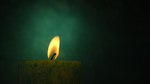Teal candle trembling flame out of the dark and blown out Footage